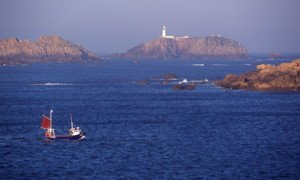 A fishing boat passes Round Island lighthouse Isles of Scilly, Cornwall, UK.